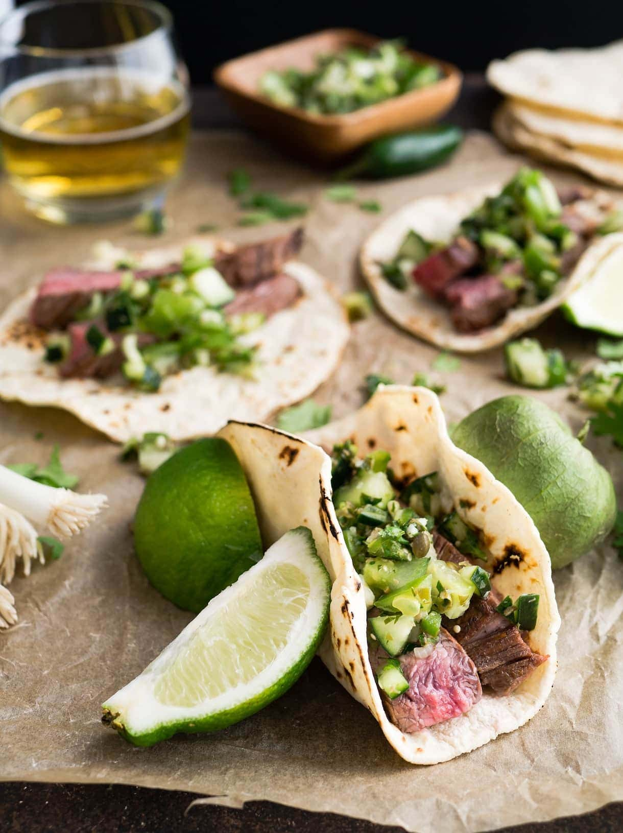 steak tacos with salsa verde, limes in backround as well as glass of beer