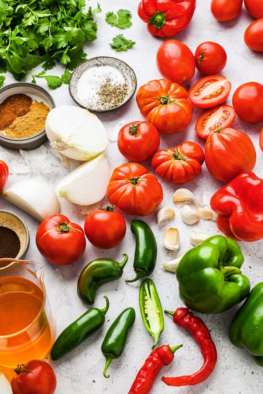 ingredients for canning salsa, with tomatoes, garlic, peppers, onions