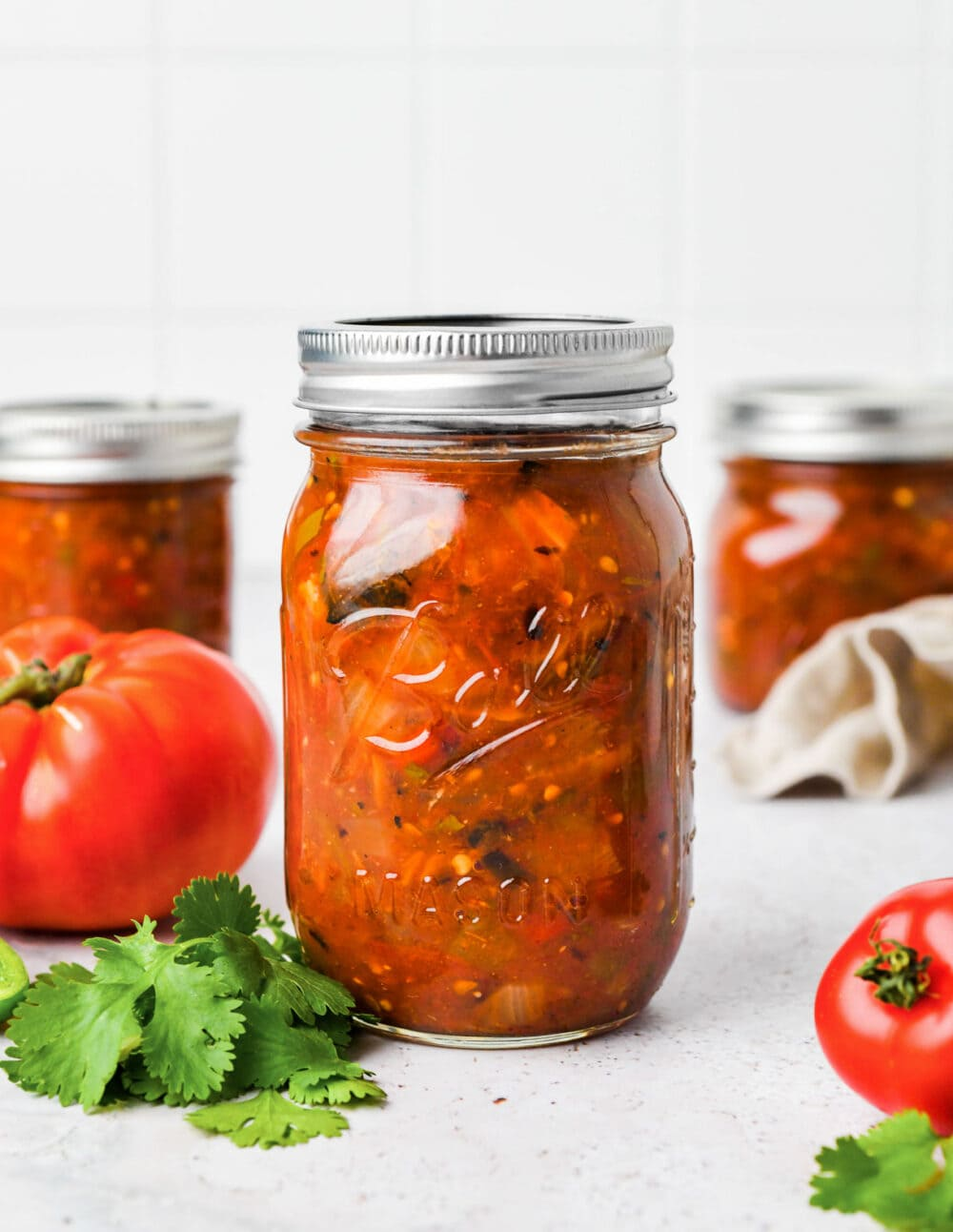 canned salsa in ball mason jars, surrounded by a few tomatoes
