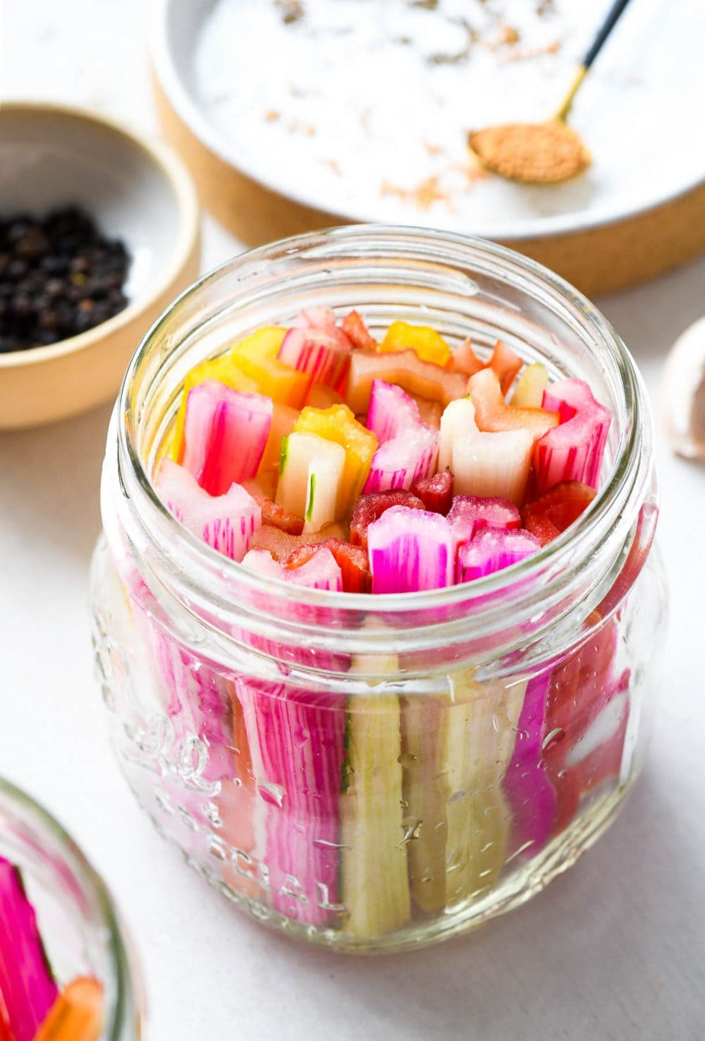 swiss chard stems in a clear jar, with peppercorns and spices in the backround
