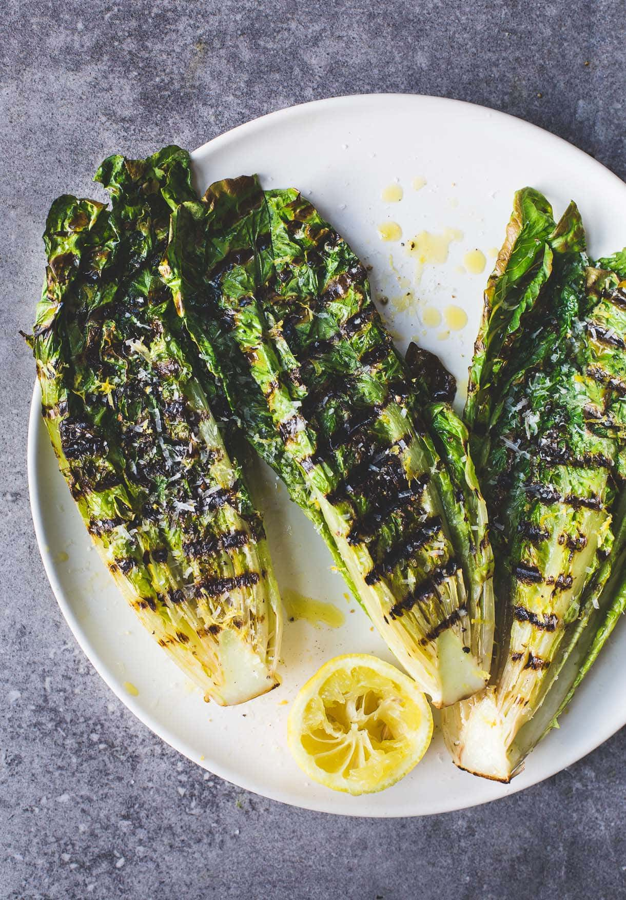 Simple Italian Grilled Romaine Lettuce Salad on a plate with half lemon