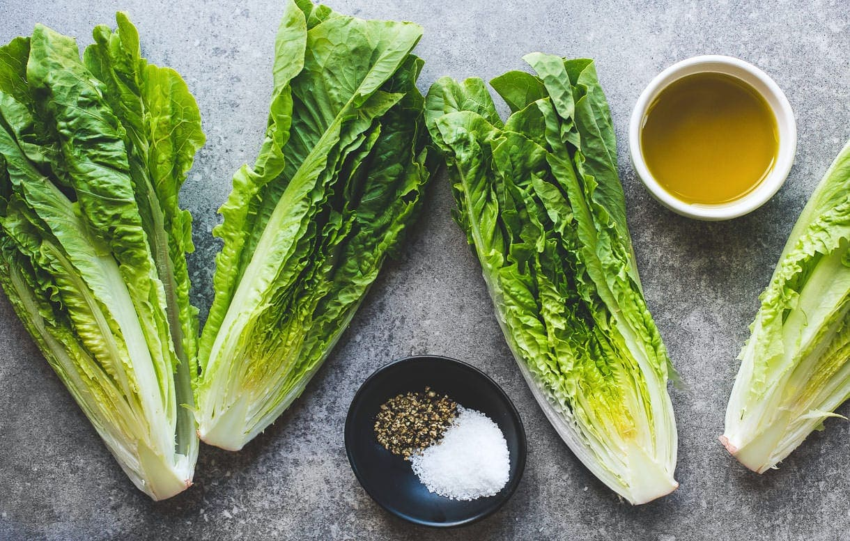 romaine lettuce, overhead image, with olive oil in a bowl, and salt pepper in a bowl
