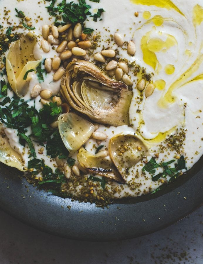 white bean hummus in a black bowl, topped with artichokes and pine nuts, olive oil, and parsley