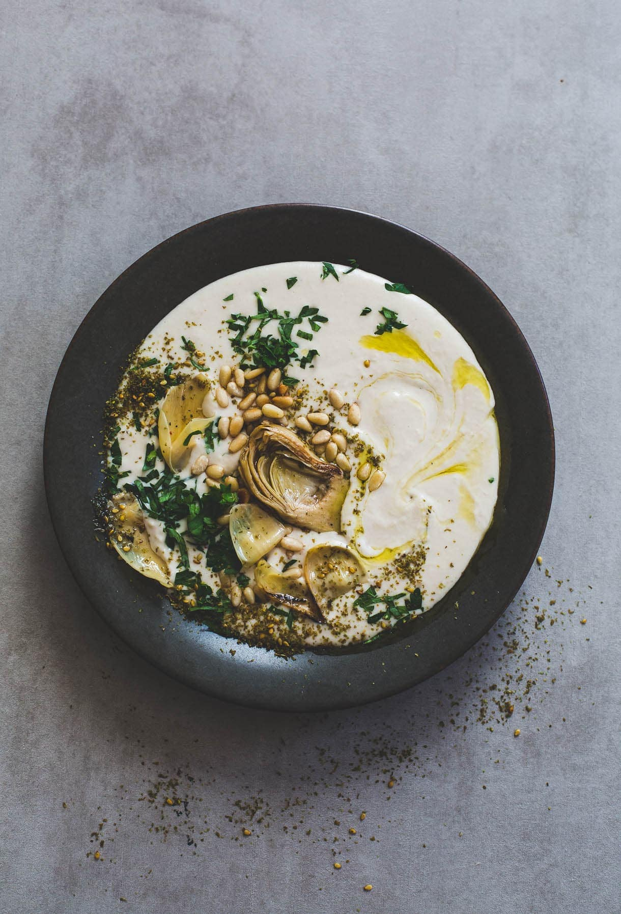 a plate of Silky White Bean Hummus with Artichokes and Pine Nuts in a black bowl