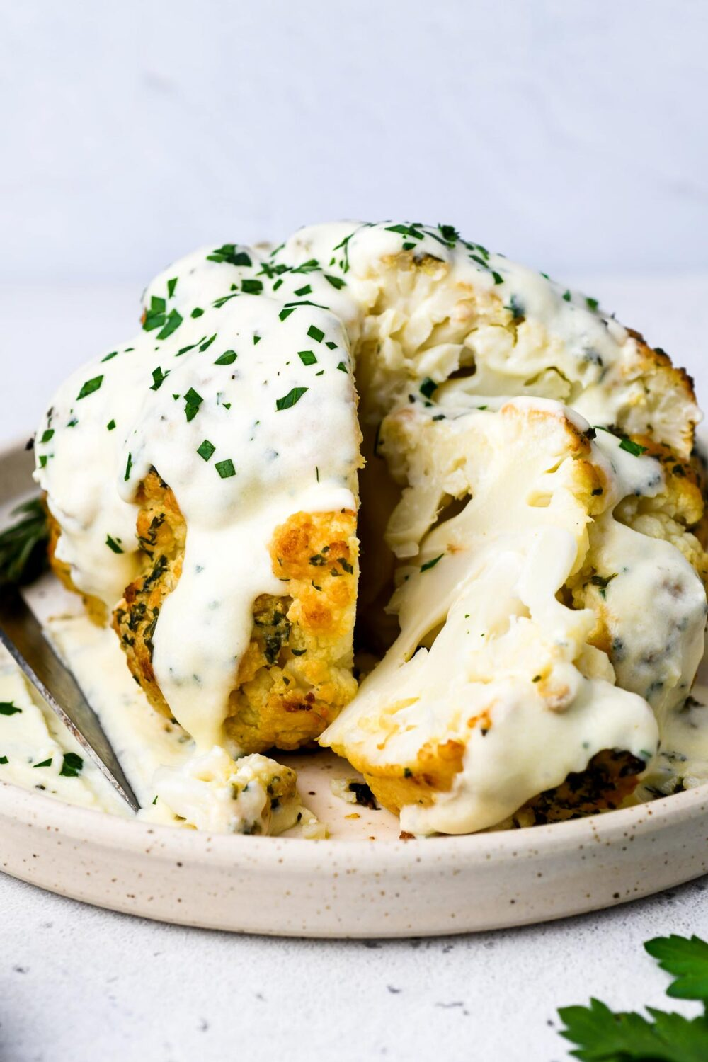 whole roasted cauliflower on a plate with cheese sauce