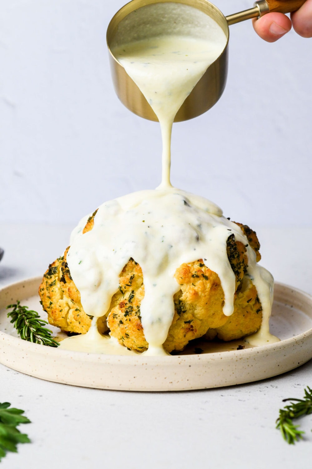 pouring cheese sauce over roasted cauliflower