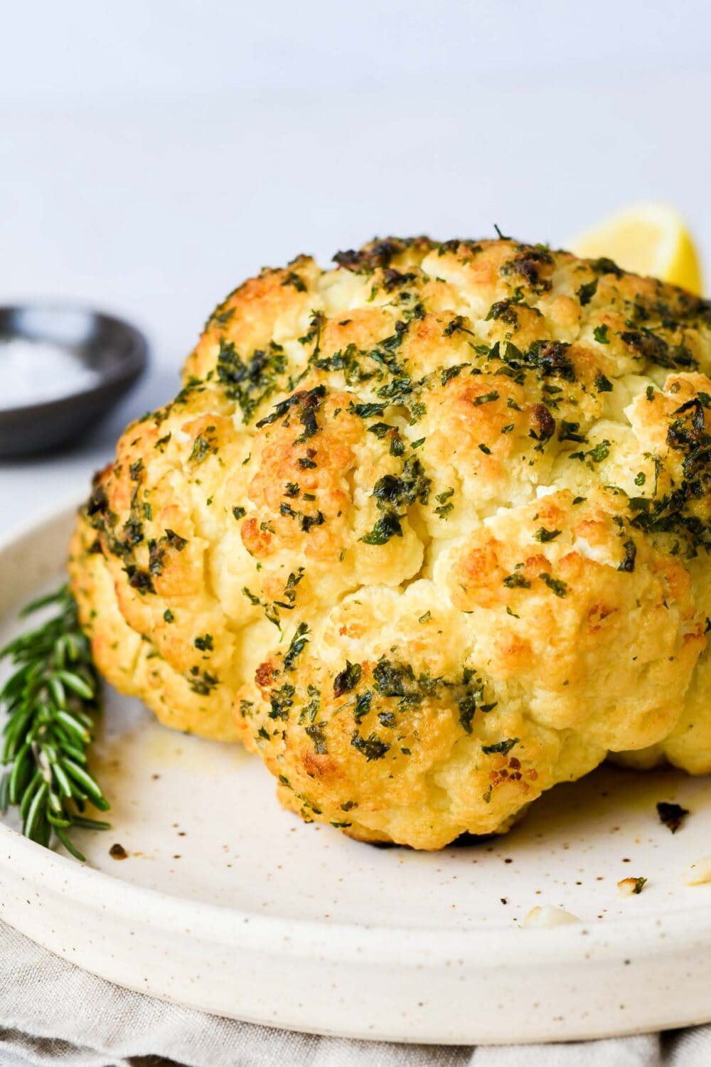 whole roasted cauliflower with herbs on a plate
