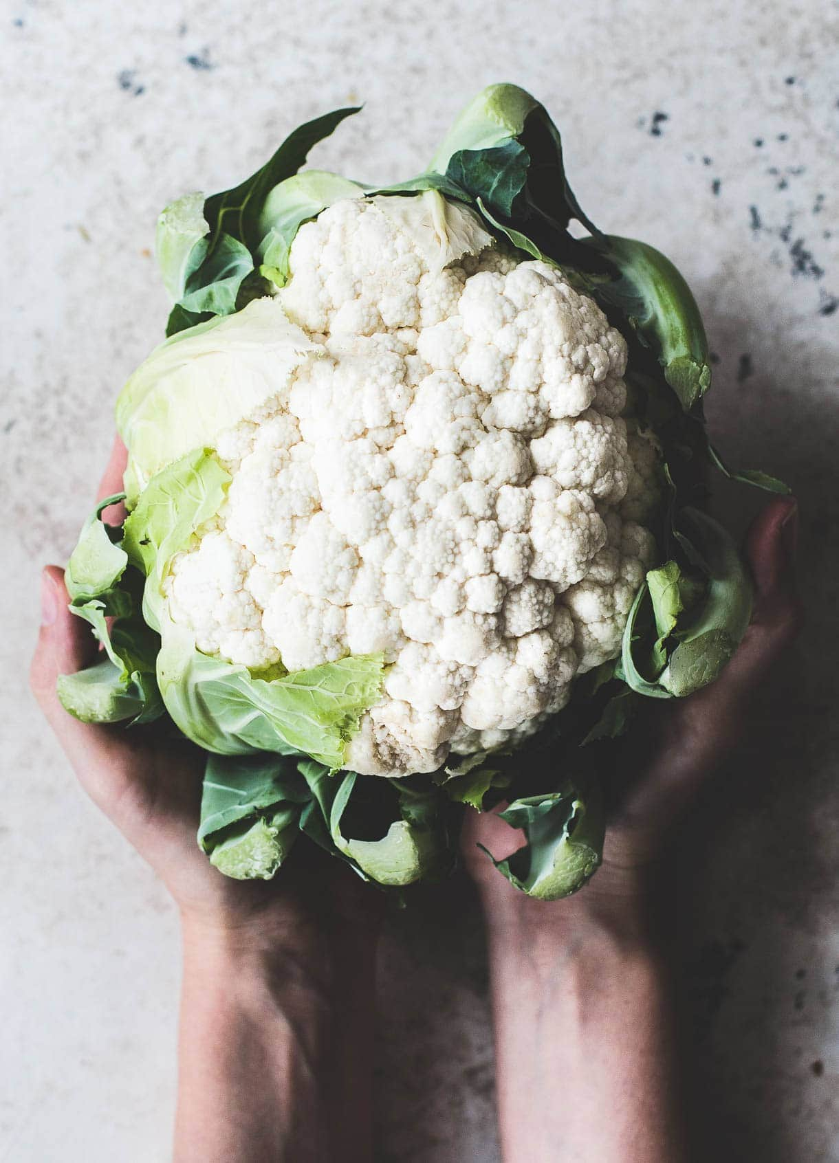 a head of cauliflower in hands, #foodstyling