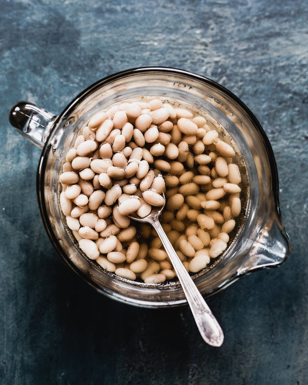 cooking great northern beans in a glass bowl with spoon