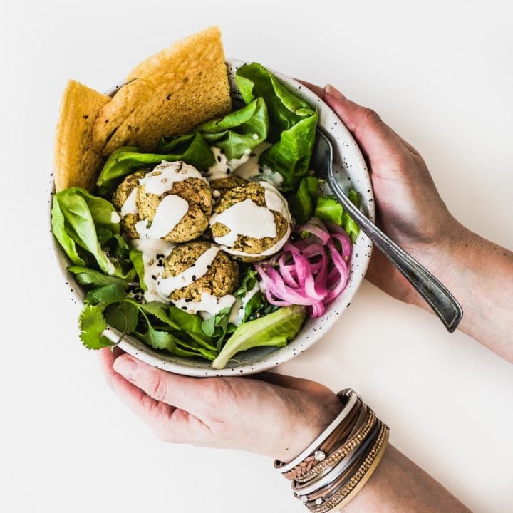 Bowl of salad topped with baked falafel, held in someone's hands, overhead angle.
