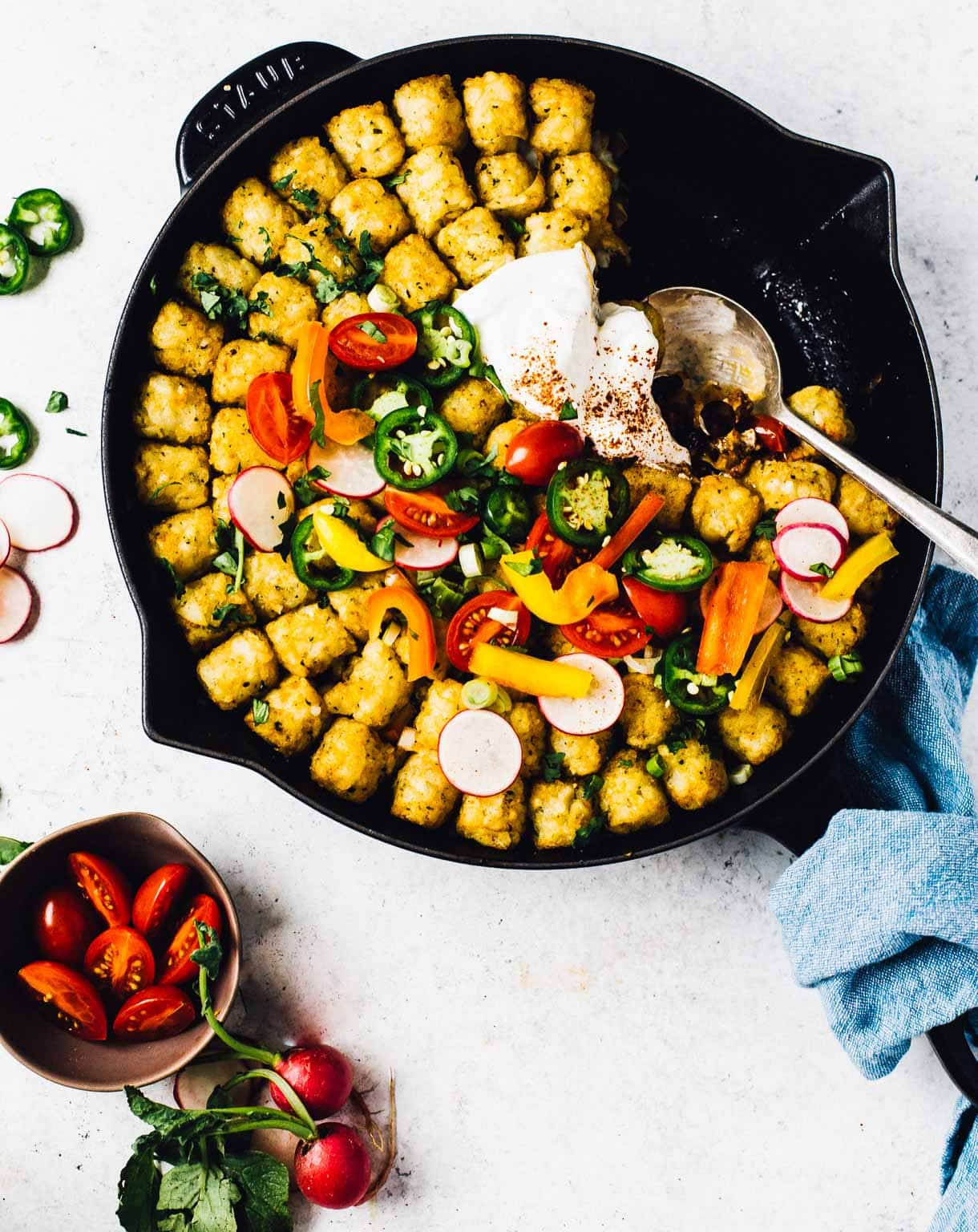 spoonful removed from taco tater tot hotdish in a cast iron skillet