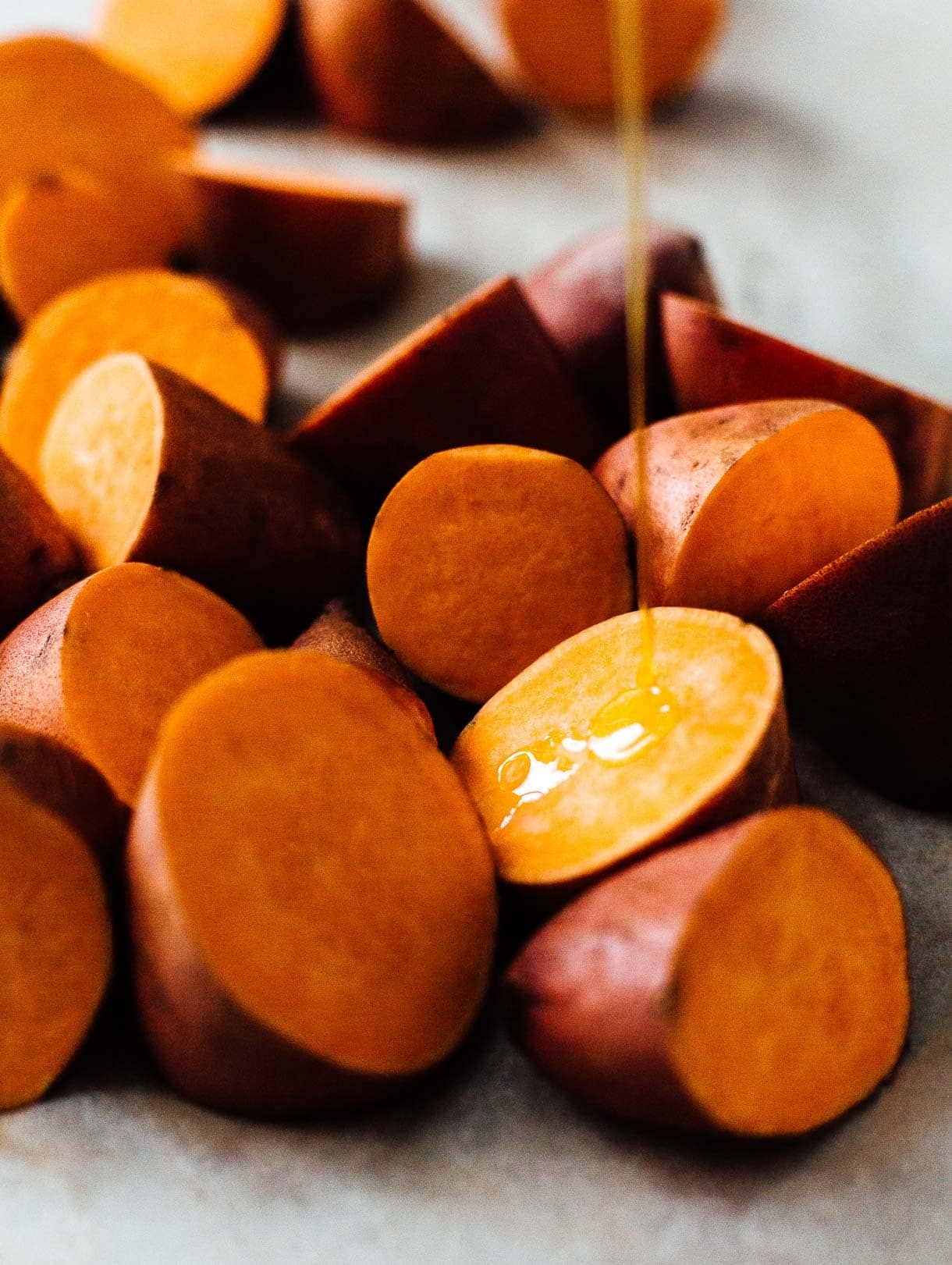 drizzling olive oil on sweet potato chunks