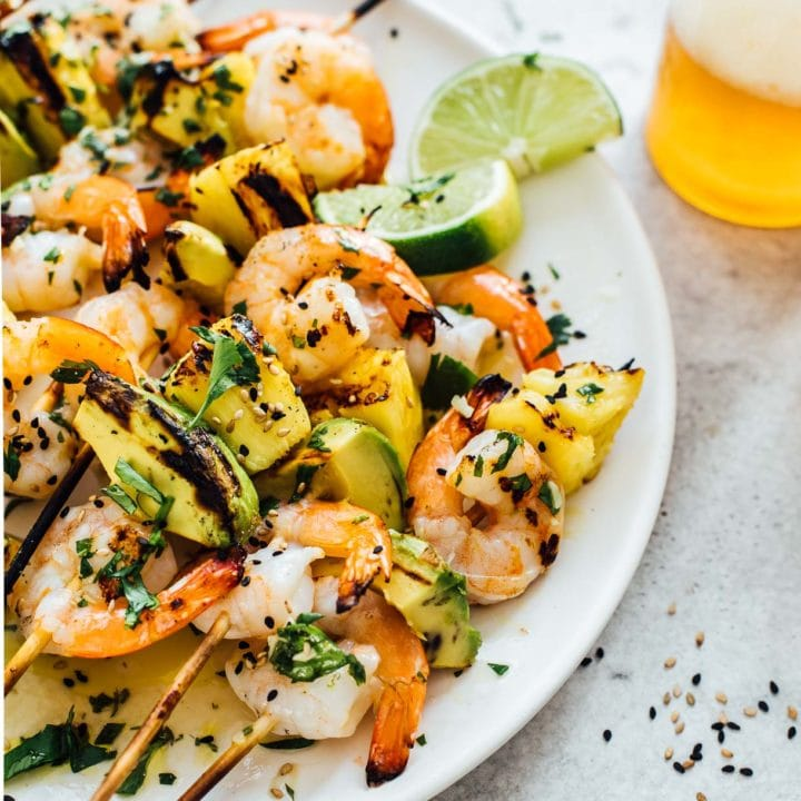 close up of grilled shrimp kabobs served with beer