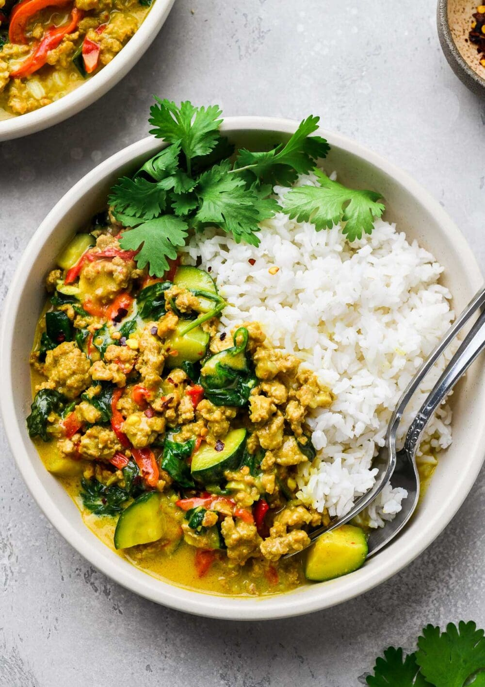ground turkey curry in a bowl with white rice, two spoons