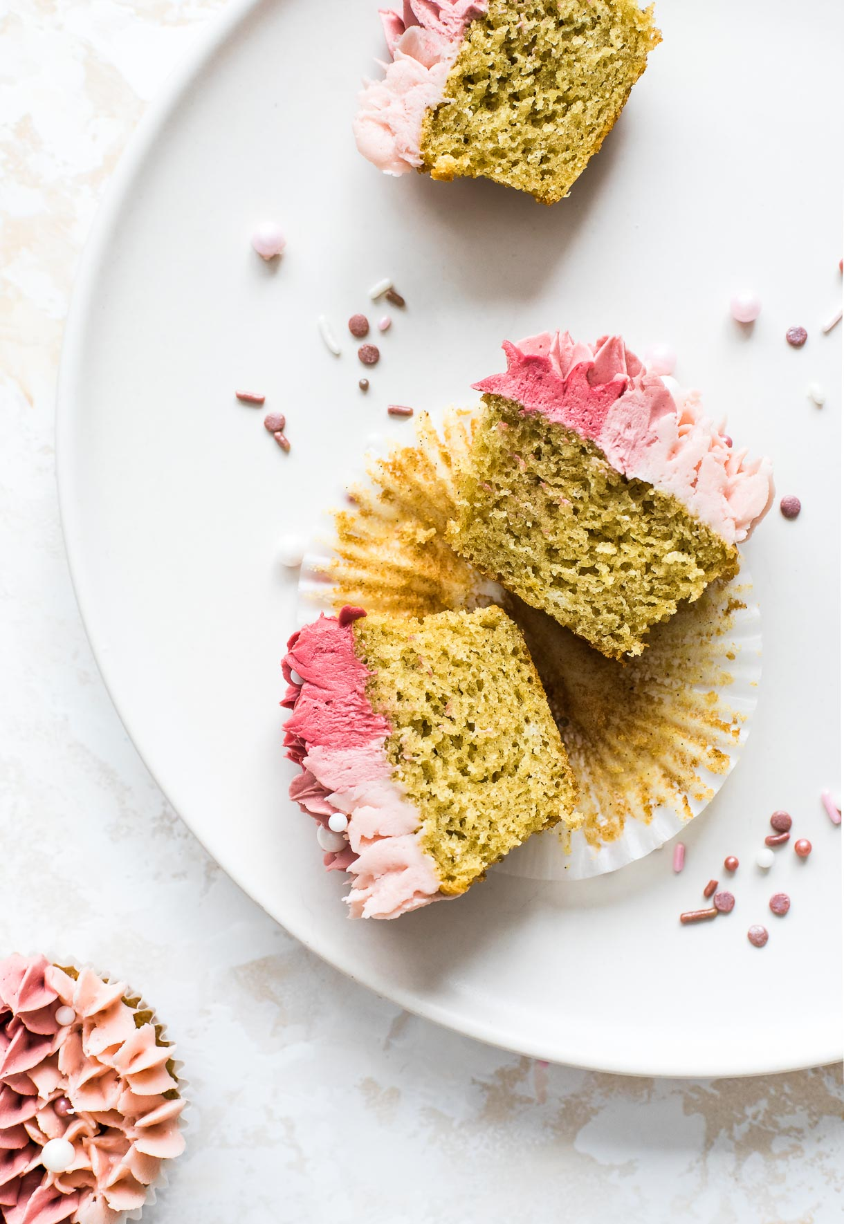 gluten free vanilla cupcakes cut open to show crumb, with pink rose sprinkles