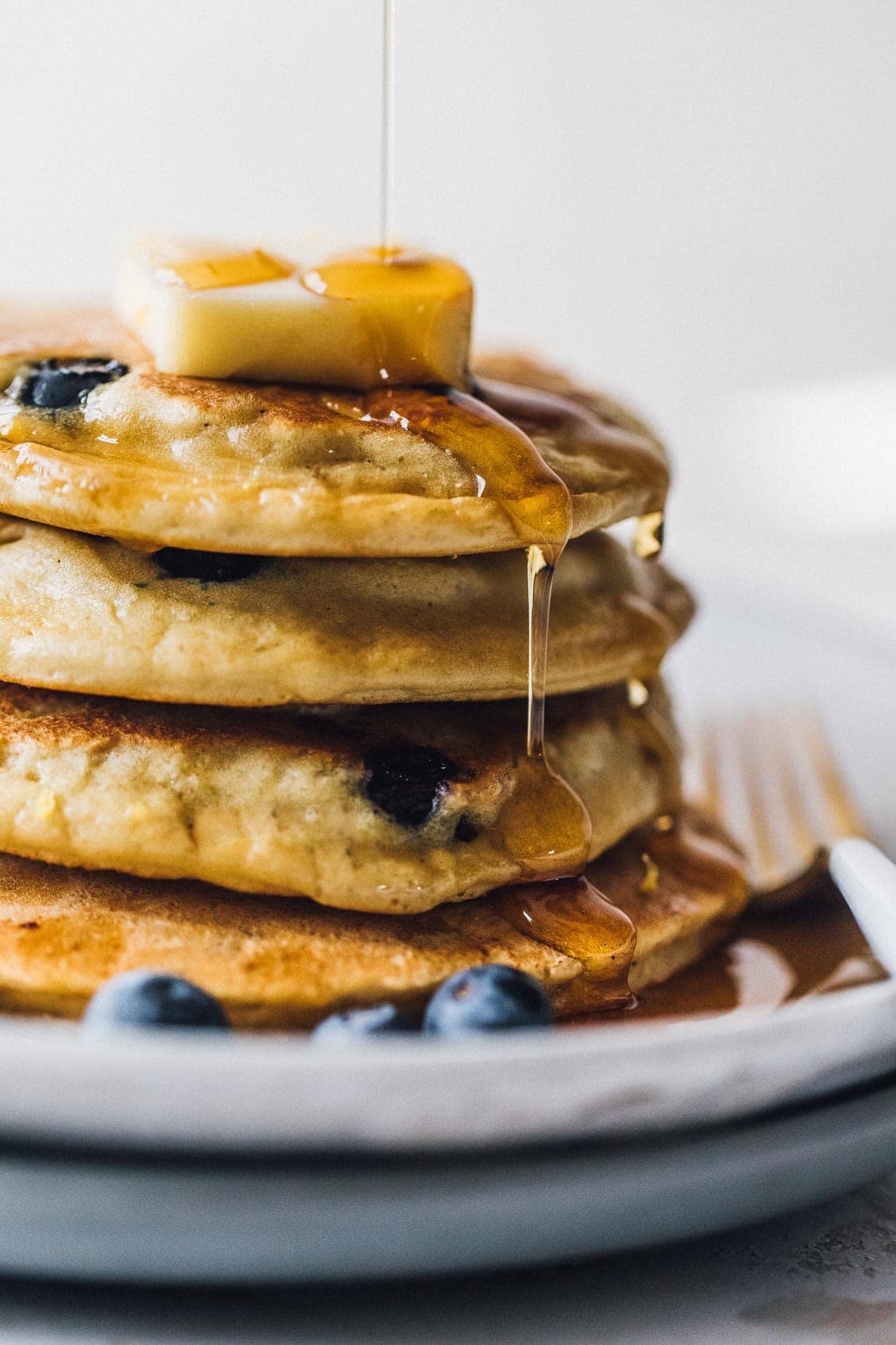 blueberry pancakes dripping with maple syrup