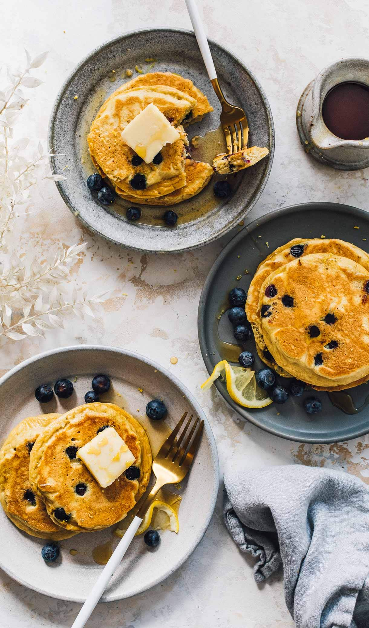 three plates of blueberry pancakes with maple syrup
