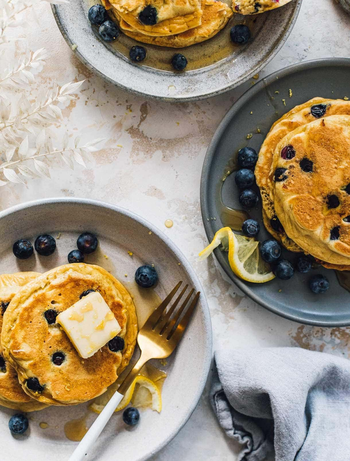 three plates with blueberry pancakes