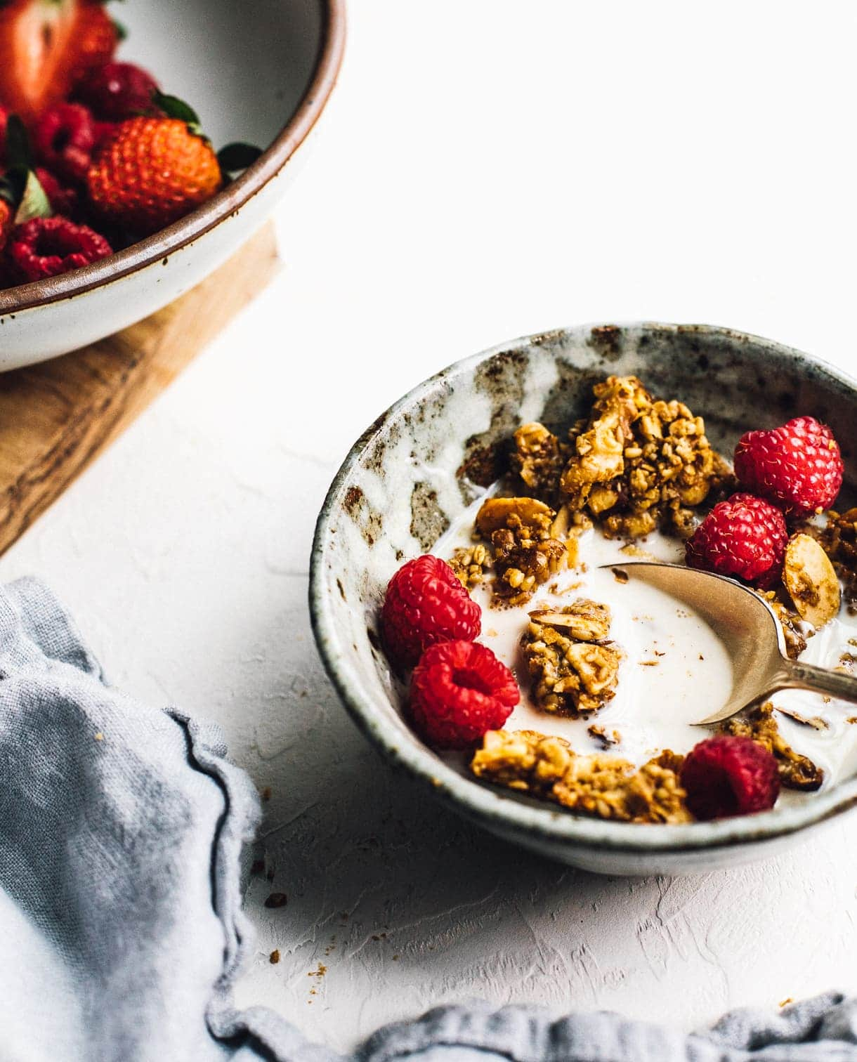 bowl of granola and milk, with bowl of raspberries in backround