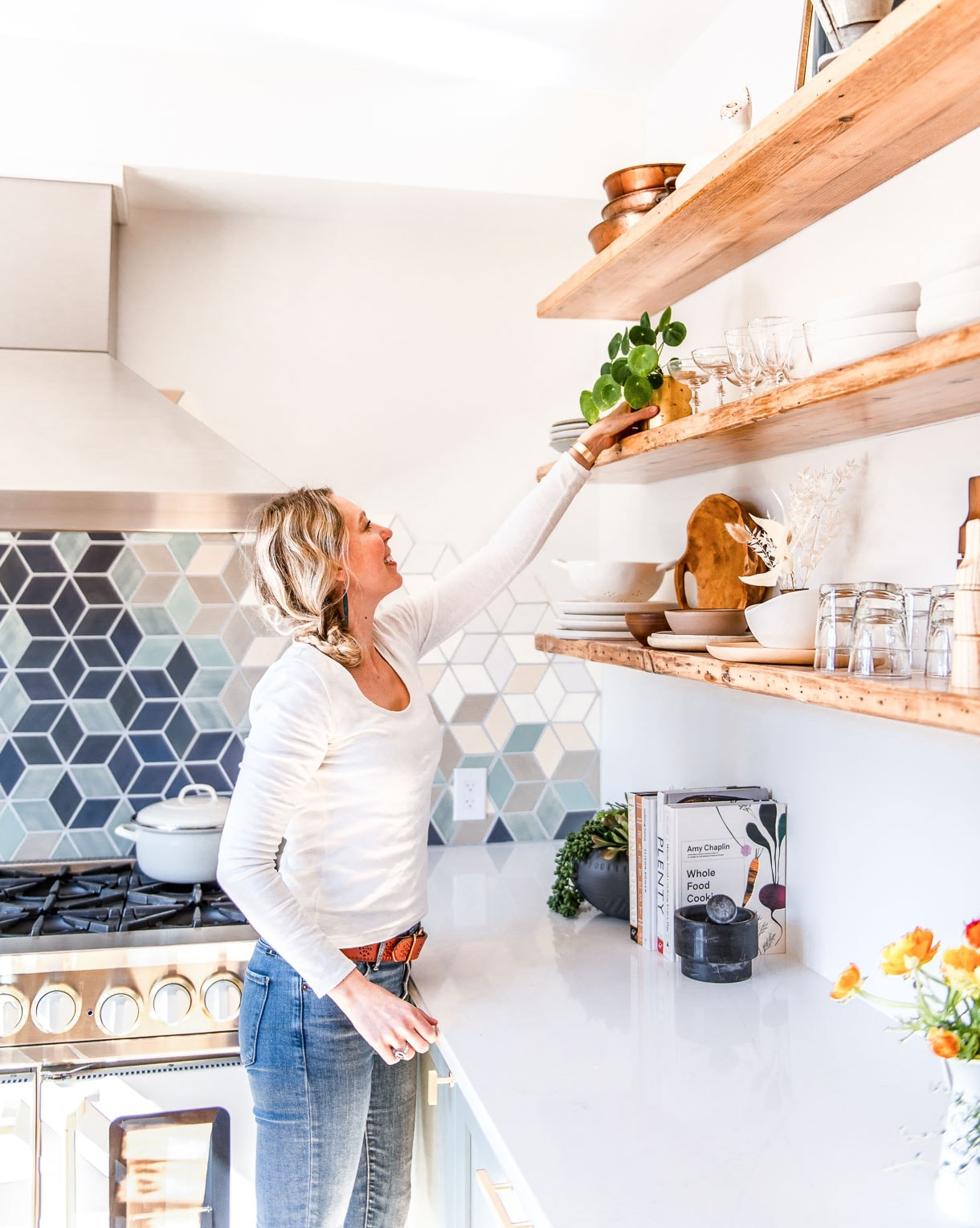 blond woman reaching to grab things off open shelving