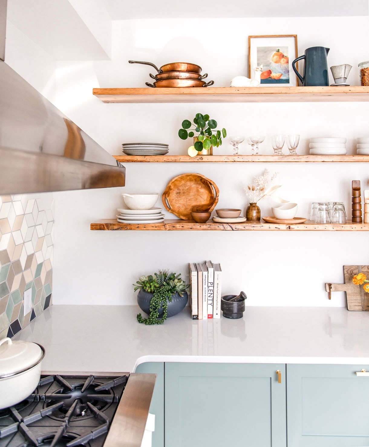 open shelving with ceramics, cookbooks in kitchen, copper cookware