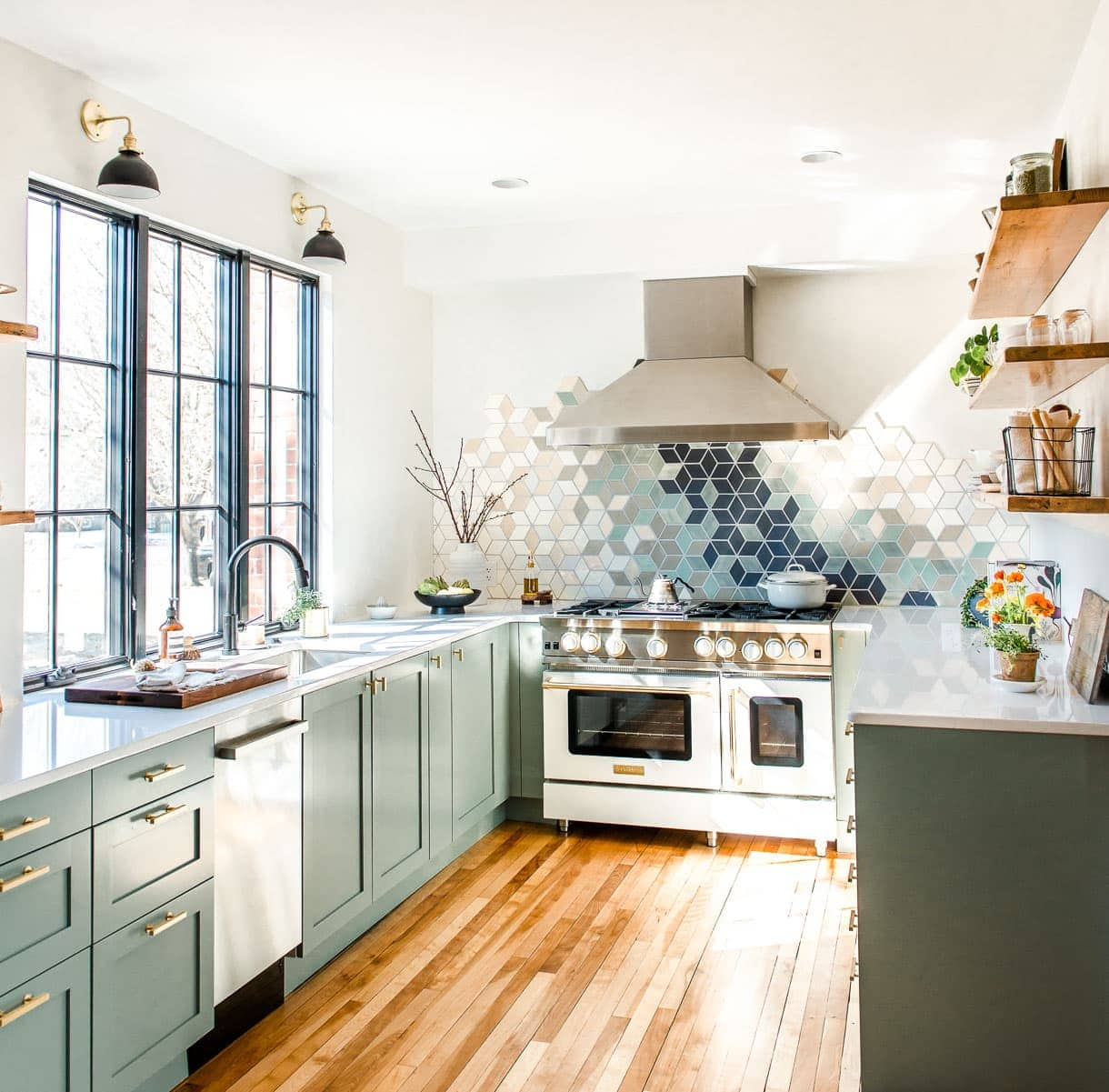 white kitchen with frameless window and sage green cabinets