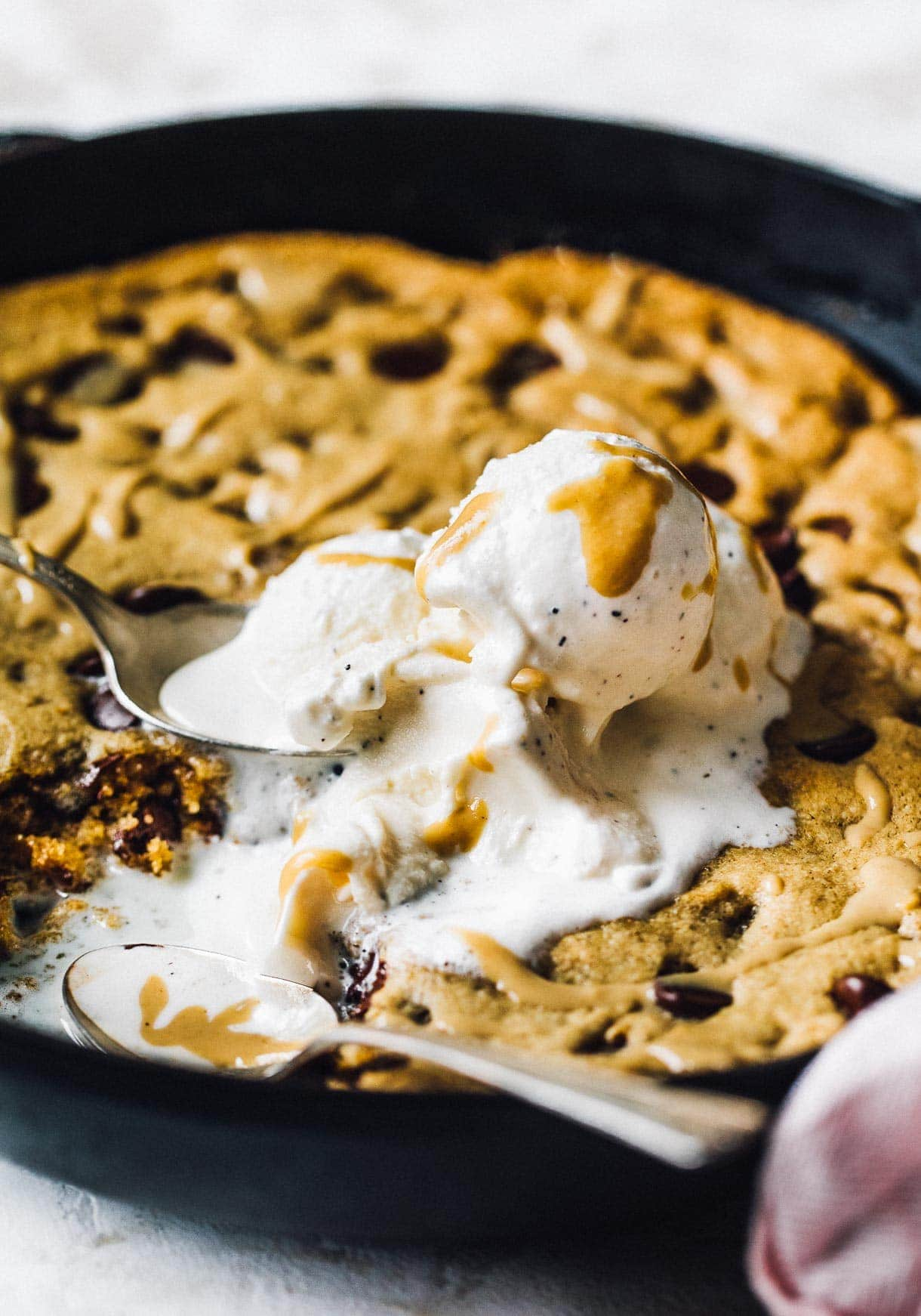 close up of chocolate chip cookie in a skillet with vanilla ice cream scoops
