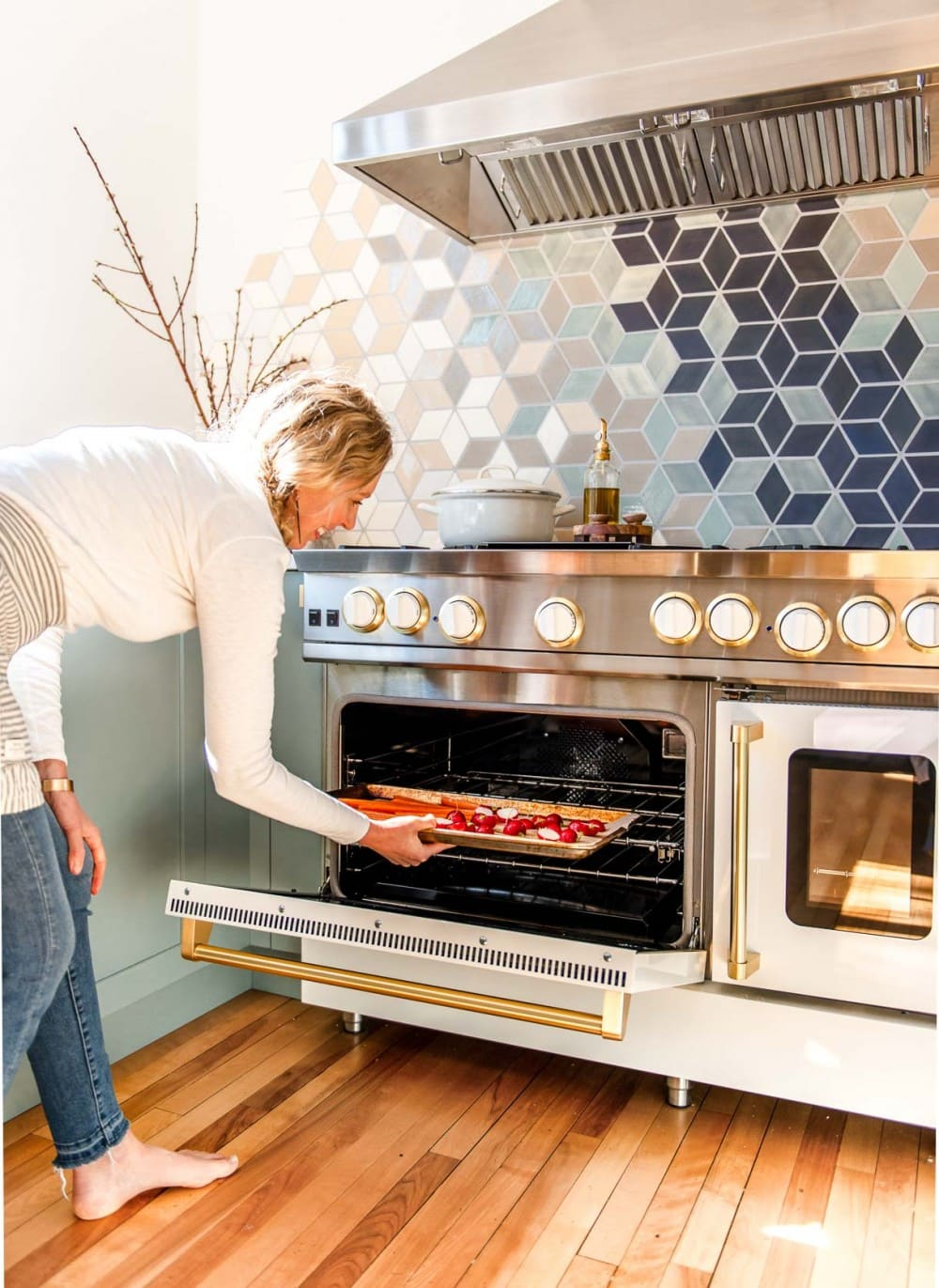 woman putting sheet pan of carrots and radishes into a white blue star oven