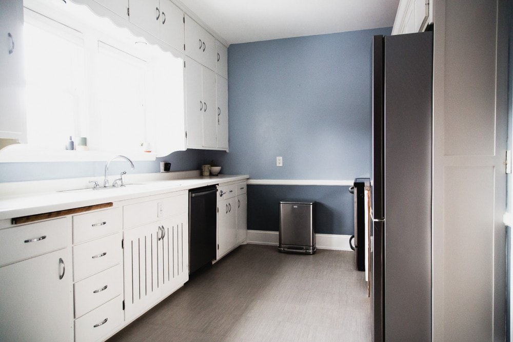 u-shaped kitchen with blue walls and white cupboards