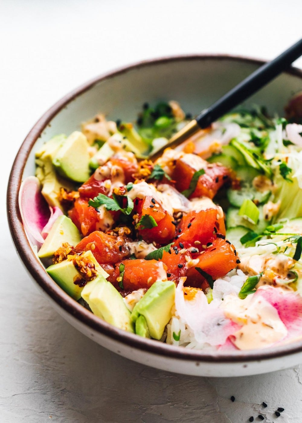 bowl of salmon poke with avocado in a bowl with a fork