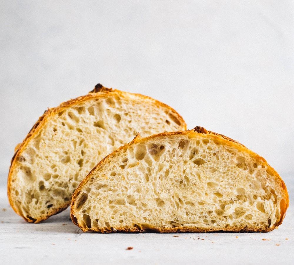 open crumb shot of sourdough bread loaf, cut in half