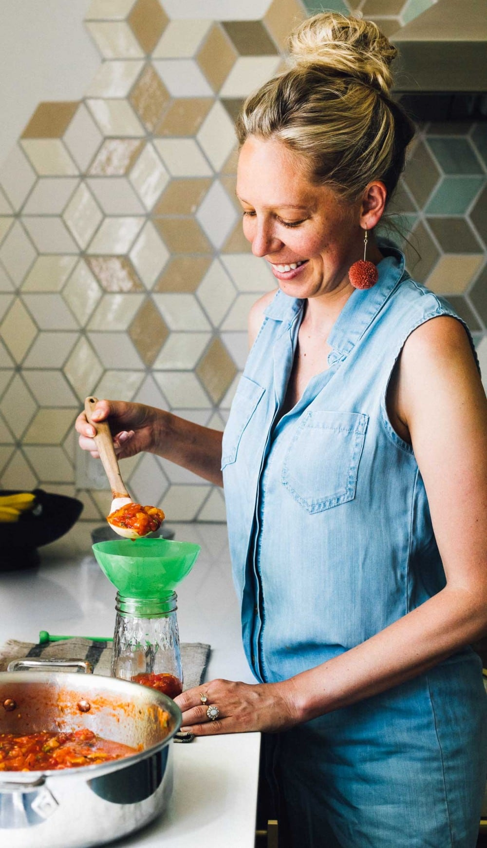 woman ladling salsa into a ball canning jar, preserving salsa