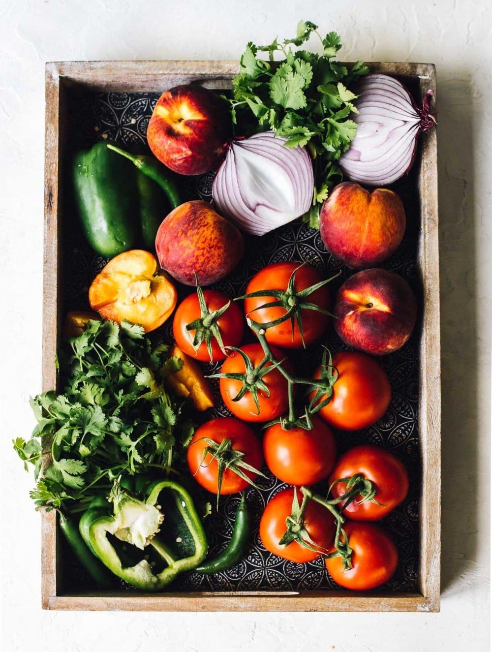 fresh tomatoes, cilantro, green pepper, onions, peaches on a tray, overhead photo