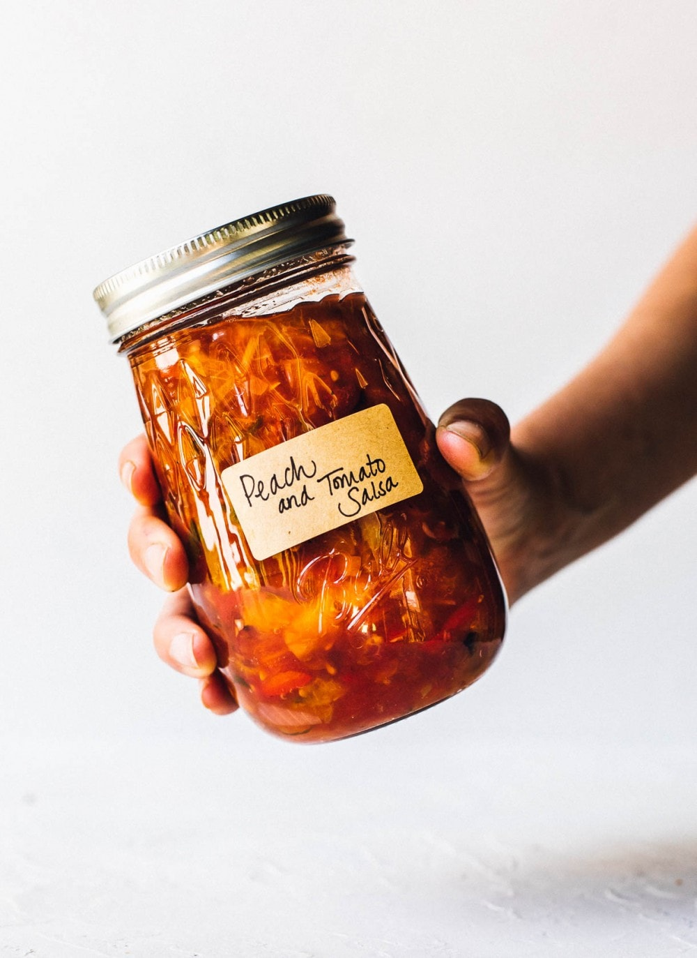 holding a jar of tomato peach salsa