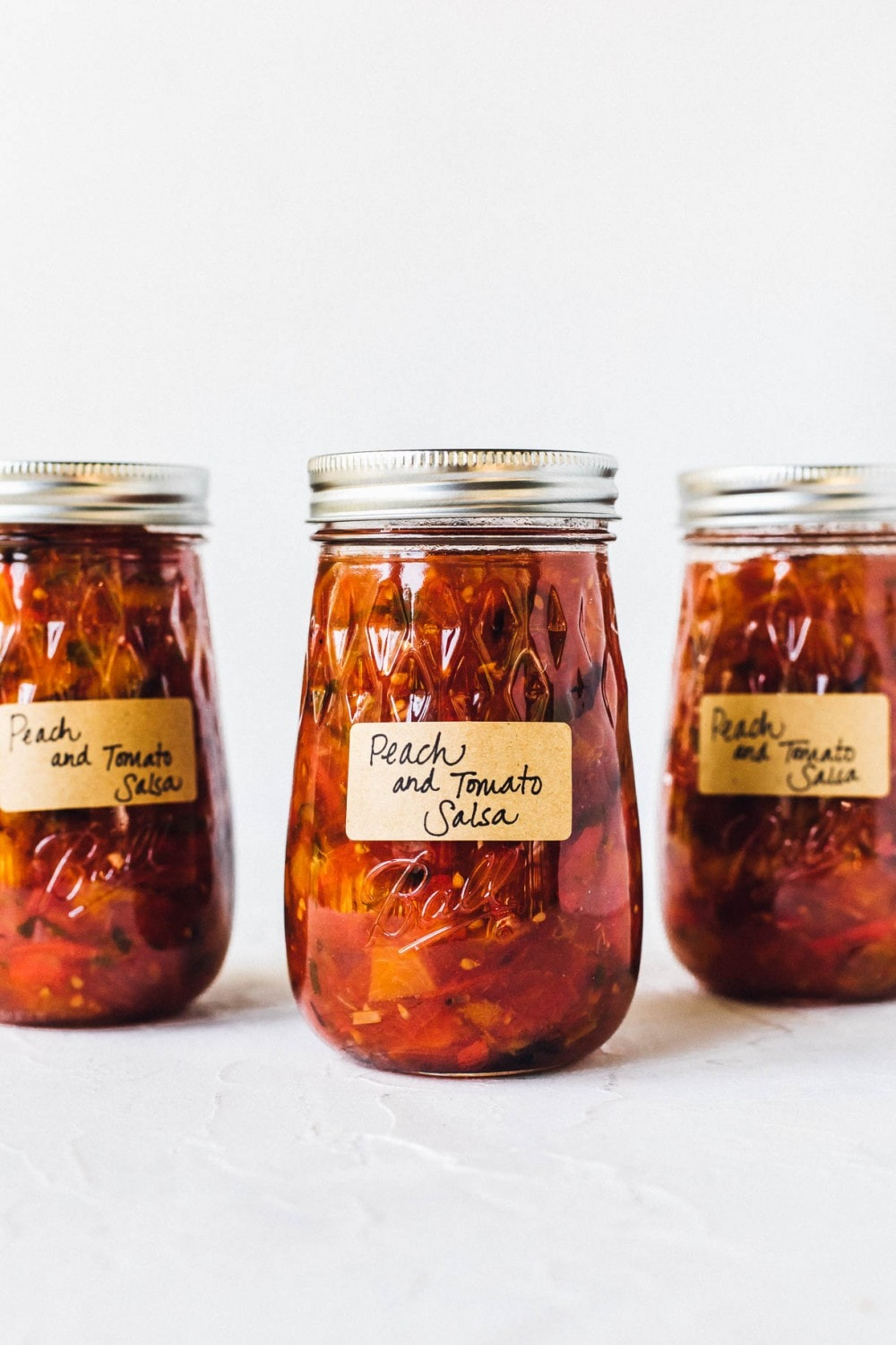 tomato peach salsa in ball canning jars with labels