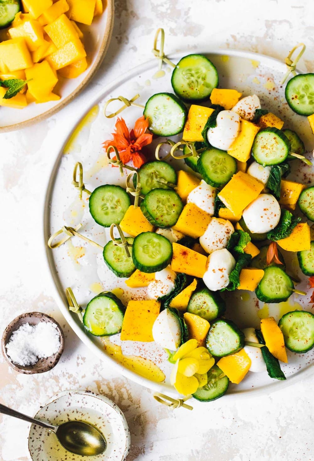 mango mozzarella cucumber skewers on a plate, with bowl of salt and white balsamic vinegar next to it