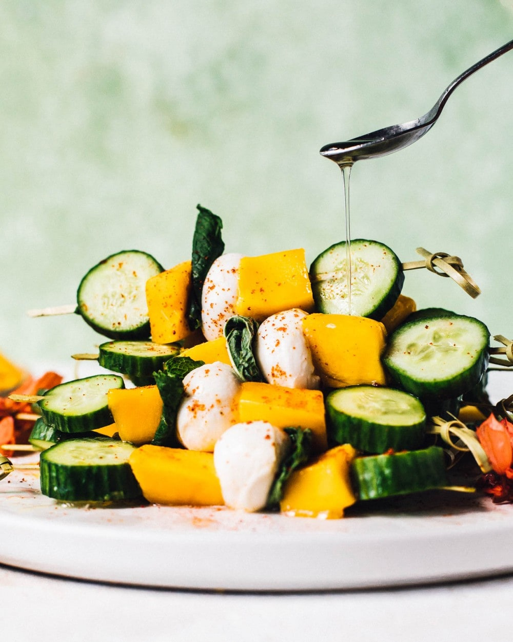 drizzling white balsamic vinegar over cucumber mango skewers stacked on a white plate
