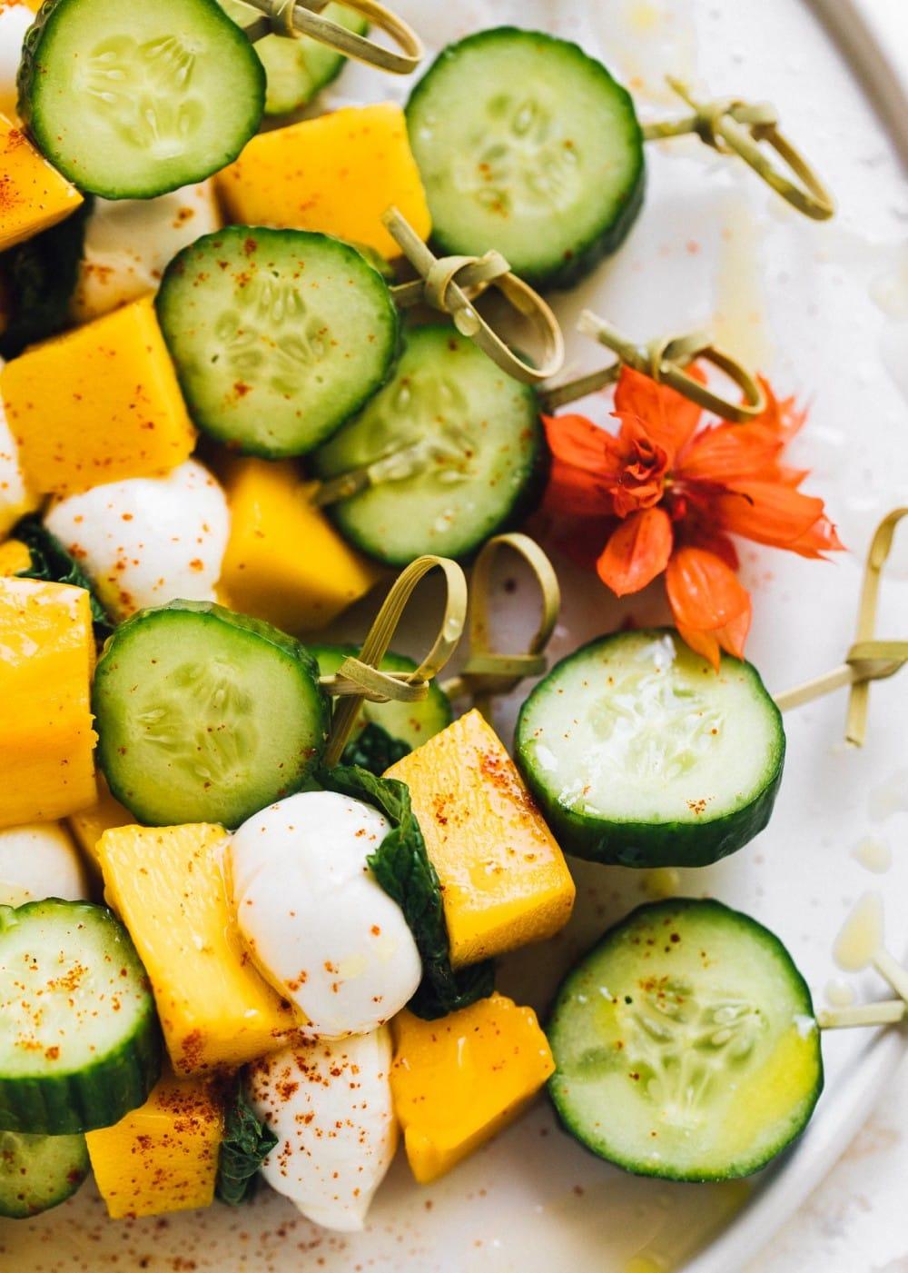 cucumber mango mozzarella skewers on a white plate