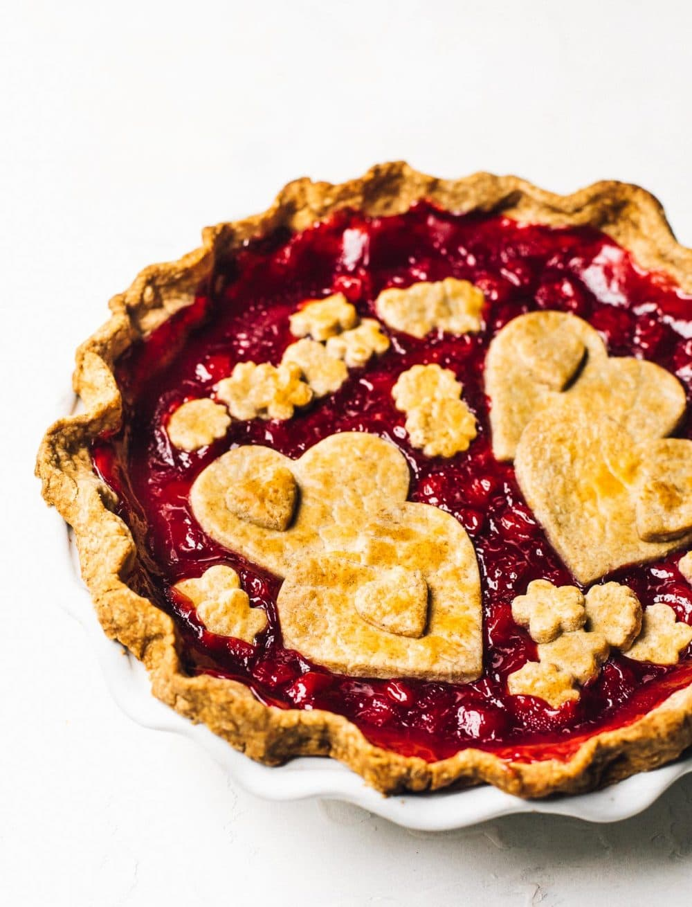 tart cherry pie in a white pie plate, with heart shapes on top cut from pastry