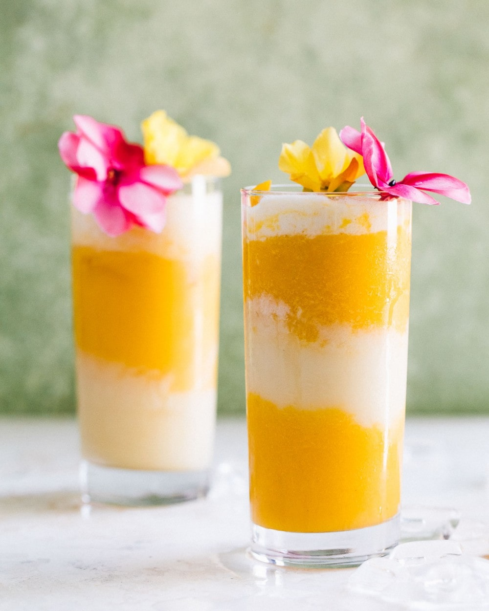 two mango and coconut cocktails with pink and yellow flowers