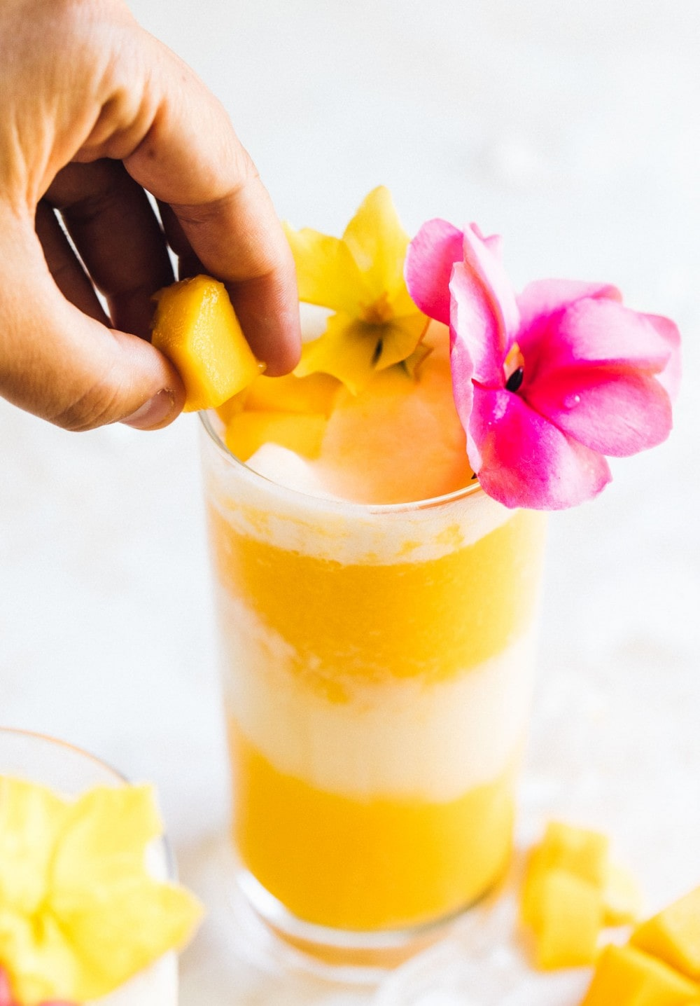 putting a mango cube onto a glass with a mango cocktail inside the glass. pink and yellow flowers are used as a garnish.