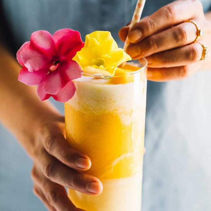 girl holding a mango lava flow cocktail, with one yellow and one pink flower as a garnish.