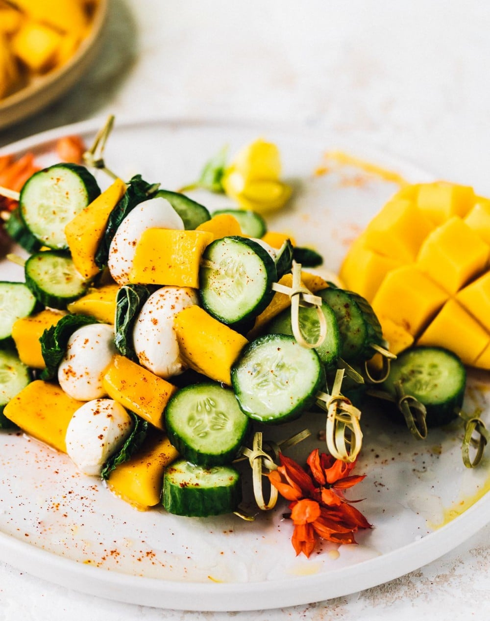 mango mozzarella skewers stacked on a plate