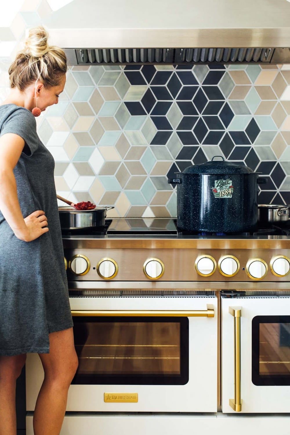 girl standing at stove with ball water bath canner on stove and she is stirring something in a saucepan