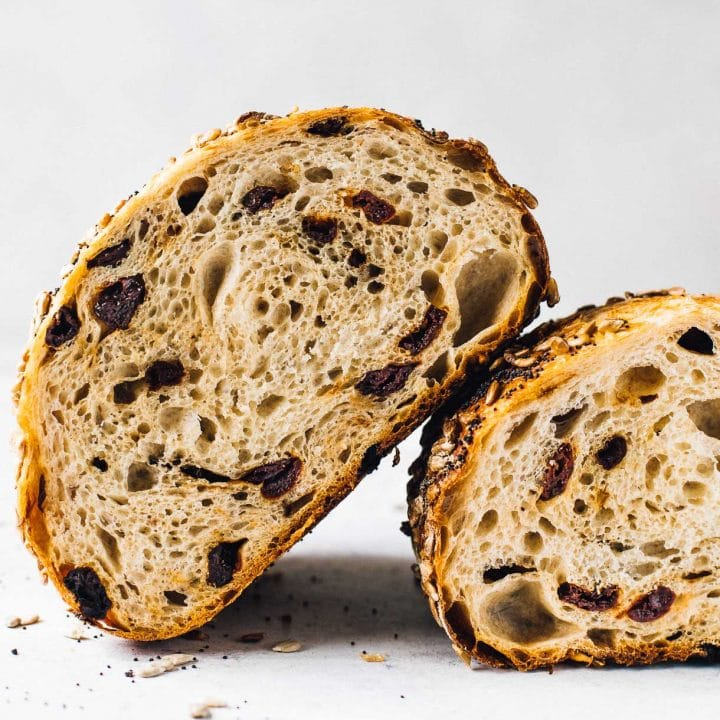 tart cherry sourdough bread, a loaf cut in half and showing the interior crumb