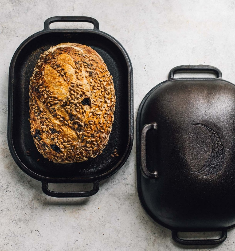 seeded sourdough bread showing resting in a cast iron baking pan