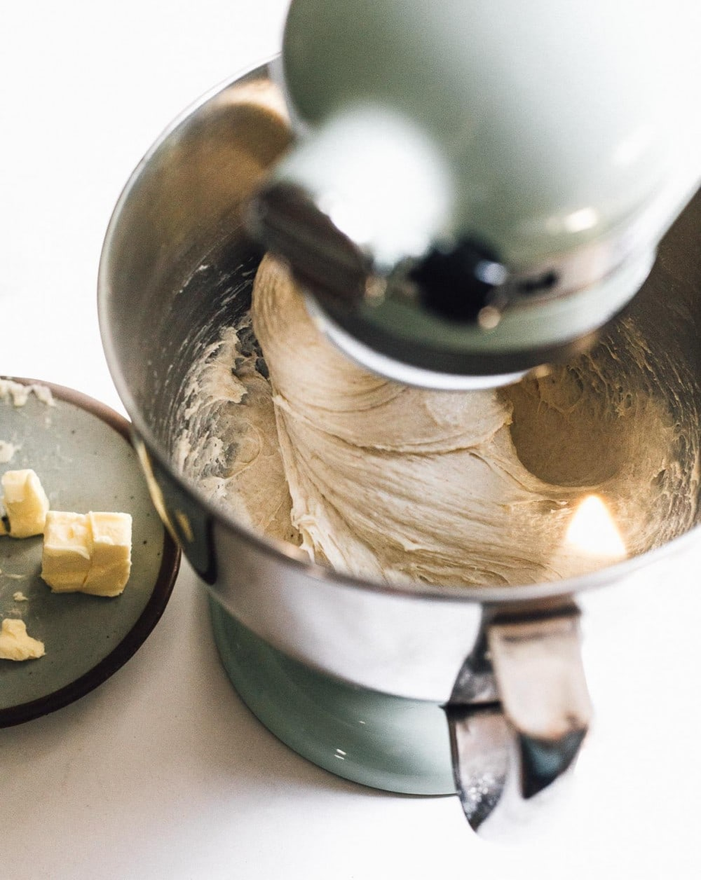 cinnamon roll dough being mixed in  a kitchenaid stand mixer, with butter on plate to its left