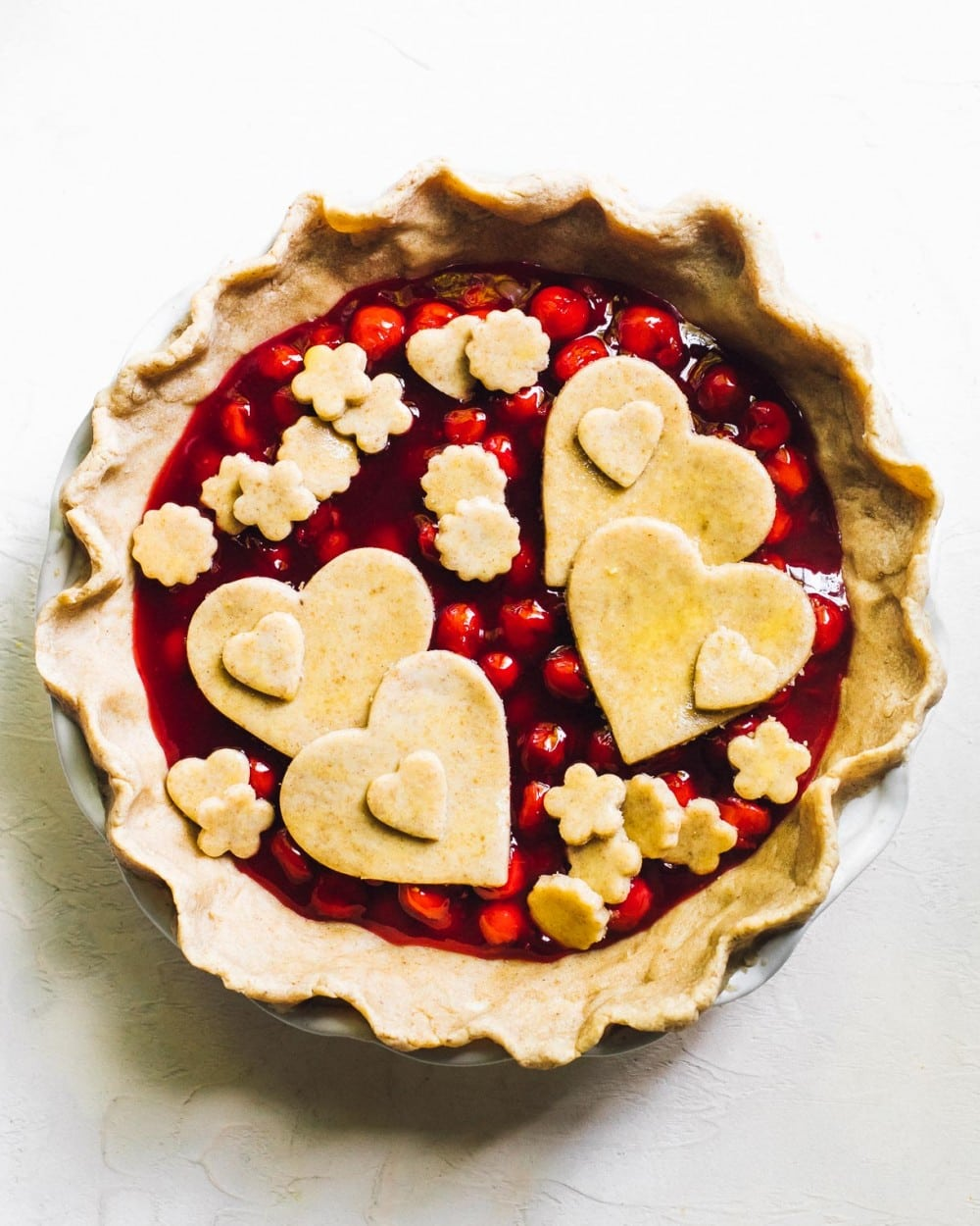 unbaked gluten free cherry pie with hearts on top for the pie crust