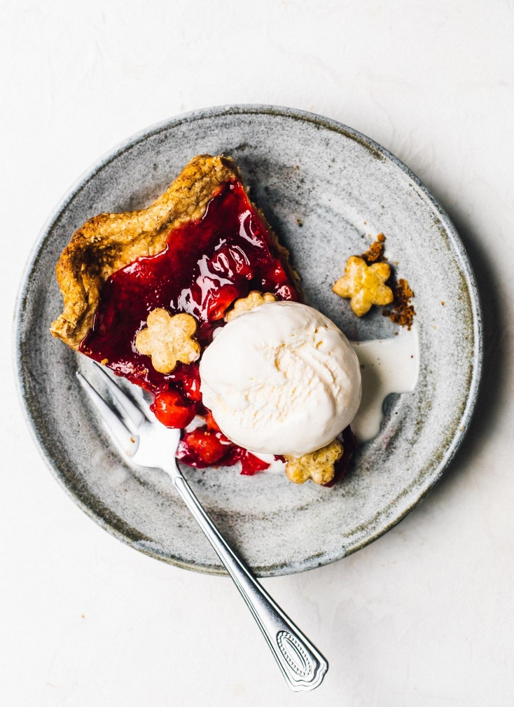 tart cherry pie on a plate with vanilla ice cream and a fork