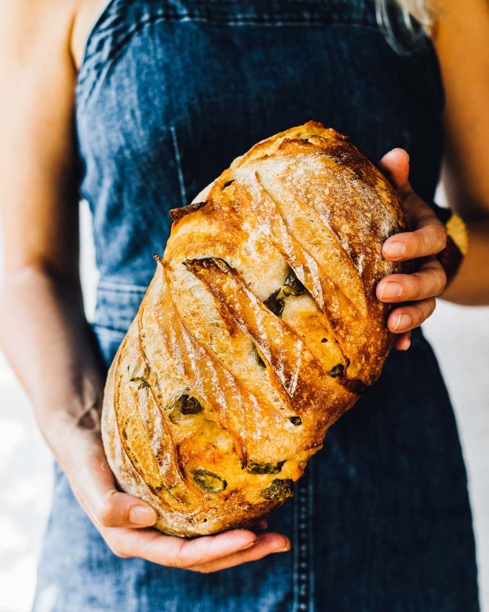 girl holding a loaf of sourdough bread with a denim dress on